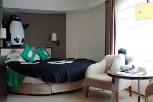 ダブルルームサイズの室内にキングサイズのベッドとソファーが2脚、液晶テレビが1台置いてある。
